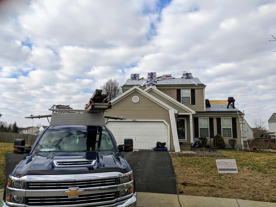 roofer tearing off and installing new asphalt shingle roof